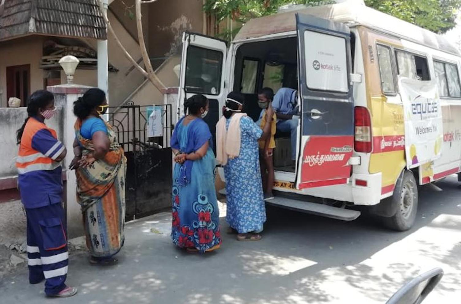 women wait in line at equitas vaccine van